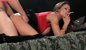 Una ragazza fuma una sigaretta durante il sesso alla pecorina