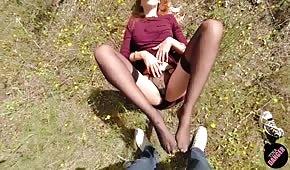 La ragazza massaggia il cazzo con i piedi all'aperto